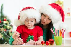 Child girl and mother writing christmas letter to. Santa Claus Stock Photo