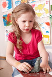Child girl mould from clay in play room. Stock Image