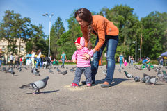 Child girl and mum playing with doves in city street Royalty Free Stock Photography
