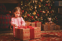 Child girl in a nightgown in Christmas night opening gifts at Ch. Child girl in a nightgown in the Christmas night opening gifts at the Christmas tree Royalty Free Stock Photography