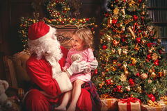 Child girl in nightgown sitting on lap of Santa Claus around Chr. Girl in a nightgown sitting on the lap of  Claus around  tree Stock Photography
