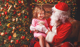 Child girl in nightgown sitting on lap of Santa Claus around Christmas  tree. Girl in ca584f0bf