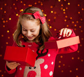 Child girl opens christmas present on dark red with lights Royalty Free Stock Image