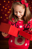 Child girl opens christmas present on dark red with lights Royalty Free Stock Images