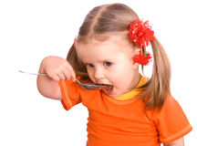 Child girl in orange with spoon eat. Stock Photo