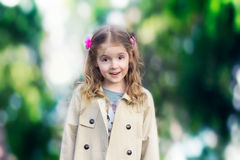 Child girl outdoors on green nature background. Stock Photos