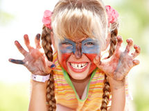 Child girl with paint on face. Stock Photo