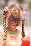 Child girl with paint on face drink  juice. Stock Photography