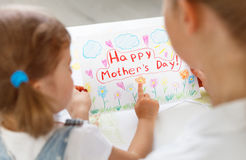 Child girl painted postcard for mom to mother`s day. Child girl painted drawing postcard for mom to mother`s day Royalty Free Stock Photography