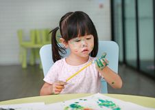 Child girl painting with paintbrush and water colors. royalty free stock photography