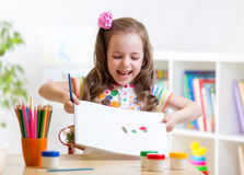 Child girl painting and showing painting in. Child girl painting and showing her painting in nursery Royalty Free Stock Image