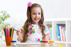 Child girl paints in her nursery Royalty Free Stock Image