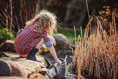 Child girl in plaid dress gathering water from pond in spring garden Stock Photography