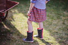 Child girl in plaid dress and rubber boots in early spring garden Royalty Free Stock Photography