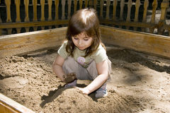 Child girl plaing at sand-box. Child girl plaing at wood sand-box in summer park, sunny points Stock Photo