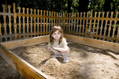 Child girl plaing at sand-box. Child girl plaing at wood sand-box in summer park, sunny points Royalty Free Stock Photography