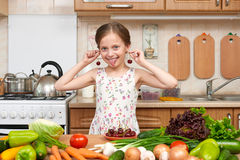 Child girl play and having fun with cherries, fruits and vegetables in home kitchen interior, healthy food concept Stock Photo