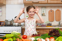 Child girl play and having fun with cherries, fruits and vegetables in home kitchen interior, healthy food concept Royalty Free Stock Images