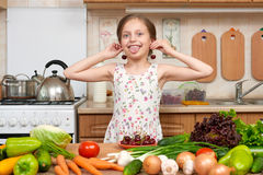 Child girl play and having fun with cherries, fruits and vegetables in home kitchen interior, healthy food concept Royalty Free Stock Photography
