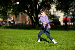 Child girl playing baseball in park. On a bright summer day Stock Image