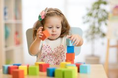 Child girl playing with block toys in day care center Stock Image