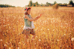 Child girl playing with blow balls on summer field Royalty Free Stock Photos