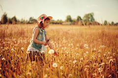Child girl playing with blow balls on summer field Royalty Free Stock Image