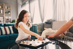Child girl playing checkers with her dad at home Royalty Free Stock Image