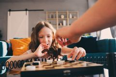 Child girl playing checkers with her dad at home Royalty Free Stock Photo