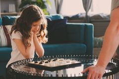 Child girl playing checkers with her dad at home Stock Images