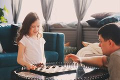 Child girl playing checkers with her dad at home Stock Photos