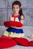 Child girl is playing with chick sitting on red pillow Stock Photography