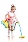 Child girl playing and cleaning room with toy vacuum cleaner stock image