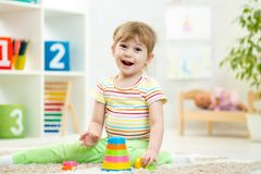 Child girl playing with colorful toys Stock Images