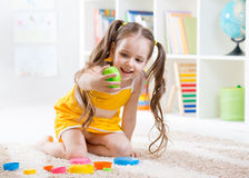 Child girl playing with colorful toys Royalty Free Stock Photos
