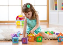 Child girl playing with constructor sitting on the floor. At home or daycare Royalty Free Stock Photo