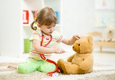 Child girl playing doctor and curing plush toy. Indoors Royalty Free Stock Image