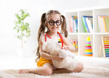 Child girl playing doctor and curing plush toy Stock Photos