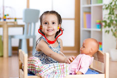 Child girl playing doctor role game examining her doll using stethoscope sitting in playroom at home, school or Royalty Free Stock Image