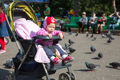 Child girl playing with doves in the city Royalty Free Stock Photos