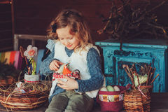 Child girl playing with easter eggs and handmade decorations in cozy country house Royalty Free Stock Photography
