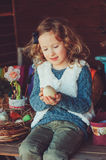 Child girl playing with easter eggs and handmade decorations in cozy country house Stock Image