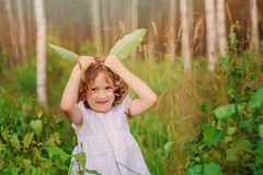 Child girl playing with green leaves in summer forest Royalty Free Stock Images
