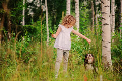 Child girl playing with her dog on the walk in summer forest Stock Image