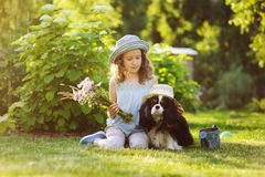 Child girl playing with her spaniel dog in summer garden, both wearing funny gardener hats. Holding bouquet of flowers Stock Photo