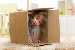 Child girl playing inside a paper box Stock Photos