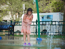 Child girl  playing in kids outdoor water park. Little girl playing in kids outdoor water park, trying to catch water by her hands Royalty Free Stock Photography