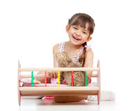 Child girl playing with a kitten and rocking him in doll crib Stock Photography