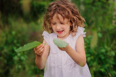 Child girl playing with leaves in summer forest with birch trees. Nature exploration with kids. Stock Photo