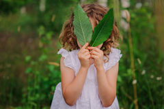 Child girl playing with leaves in summer forest with birch trees. Nature exploration with kids. Royalty Free Stock Image